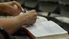 Taking Notes on a Bible during Church (devotions) - stock footage