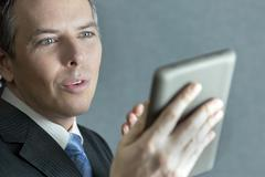 confident businessman gesturing to tablet computer - stock photo