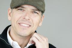 Smiling man in newsboy hat adjusts collar Stock Photos