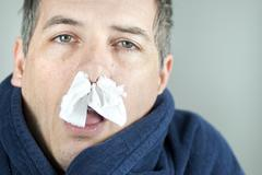 man with tissue in nose - stock photo