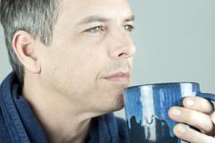 serene man holding mug looking off camera - stock photo