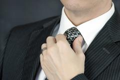 businessman adjusts tie - stock photo