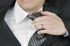 businessman tugs at tie - stock photo