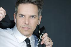 businessman wearing headphones puts on suit jacket - stock photo