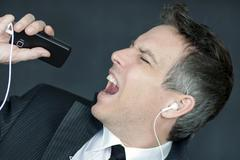 Businessman wearing headphones sings into cell phone Stock Photos