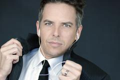 Stock Photo of confident businessman wearing headphones adjusts suit