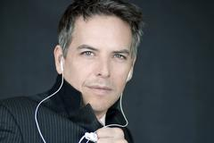 confident businessman wearing headphones holds jacket closed - stock photo