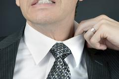 Stock Photo of uncomfortable businessman adjusts collar