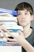 overwhelmed teen holds stack of textbooks - stock photo