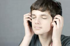 teen holding headphones to ears with eyes closed - stock photo