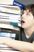 terrified teen looks up at a stack of textbooks - stock photo