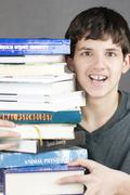 Terrified teen holds stack of textbooks Stock Photos