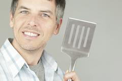 Man with bbq flipper Stock Photos