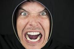 furious man looks to camera - stock photo
