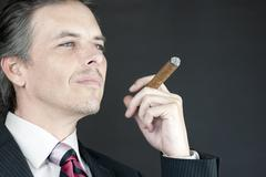 businessman holds cigar in contemplation - stock photo