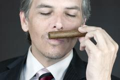 businessman smells cigar - stock photo