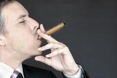 businessman smokes cigar appreciatively - stock photo