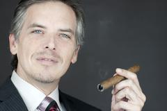 Confident businessman holds cigar Stock Photos