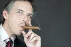 Confident businessman smokes cigar, side Stock Photos