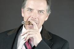 Confident businessman smokes cigar Stock Photos