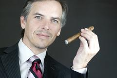 Elegant businessman holds cigar Stock Photos