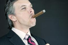 Successful businessman enjoys cigar Stock Photos