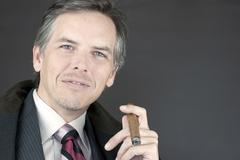 successful businessman holds cigar - stock photo