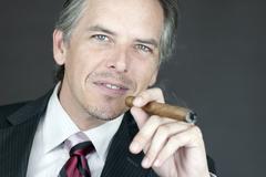 successful businessman smokes cigar - stock photo