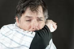 man stifles sneeze in elbow - stock photo