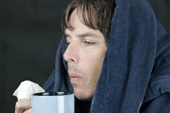 sick man blowing on hot mug - stock photo