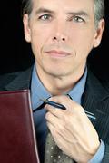 worried businessman adjusts tie - stock photo