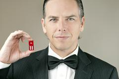 Confident man in tux holding dice Stock Photos