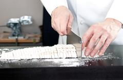 chef cutting noodles, pasta roller in background - stock photo