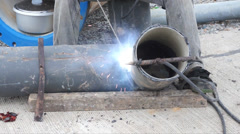 Stock Video Footage of Welder uses torch for welding pipe metal on site.