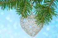 Stock Photo of silver heart on the fir branch