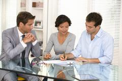 Couple with real-estate agent signing home investment contract - stock photo
