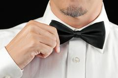 Man in tux straightens bowtie, one hand Stock Photos