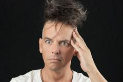 Man thinks, looking off camera, hair piled on head Stock Photos