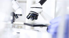 Researcher working in lab with microscope, close up Stock Footage