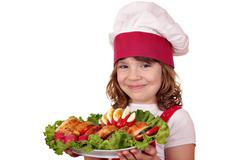 Beautiful little girl cook with roasted chicken meat and salad Stock Photos