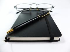 Black Notebook with Pen and Glasses Isolated on White Stock Photos