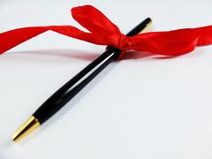 Pen With Red Bow on a White Background Stock Photos
