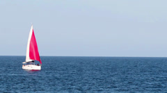 Yacht with a red sail on the sea Stock Footage