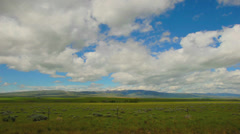 Wide time-lapse of clouds over a field in Montana - stock footage