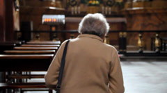 Lady prays at alter in church 2 Stock Footage