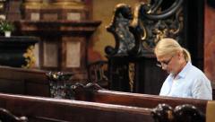 Lady prays sitting church Stock Footage