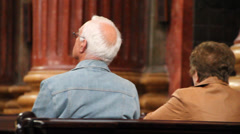Old couple sit in church Stock Footage