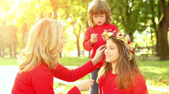 Mother and daughters having some good time in autumn park Stock Footage