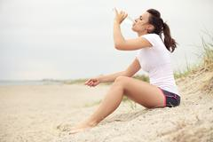 woman at the beach drinking water - stock photo