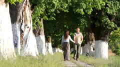 Couple of two lovers walk to alley with trees, lady step to back Stock Footage